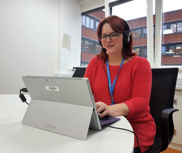A lady (Tanya) working at a laptop with a headset on.