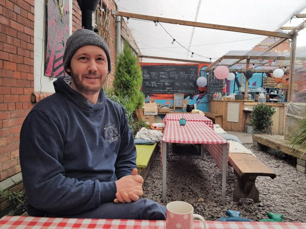 The co-founder of Dusty Knuckle Pizza, Phil Lewis, smiling at the camera in his restaurant.