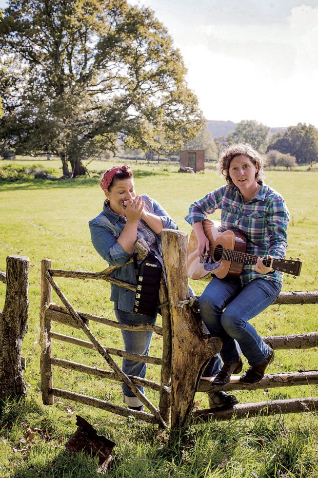 Sam and Shauna in a sunny field resting by a gate and Shauna is playing guitar