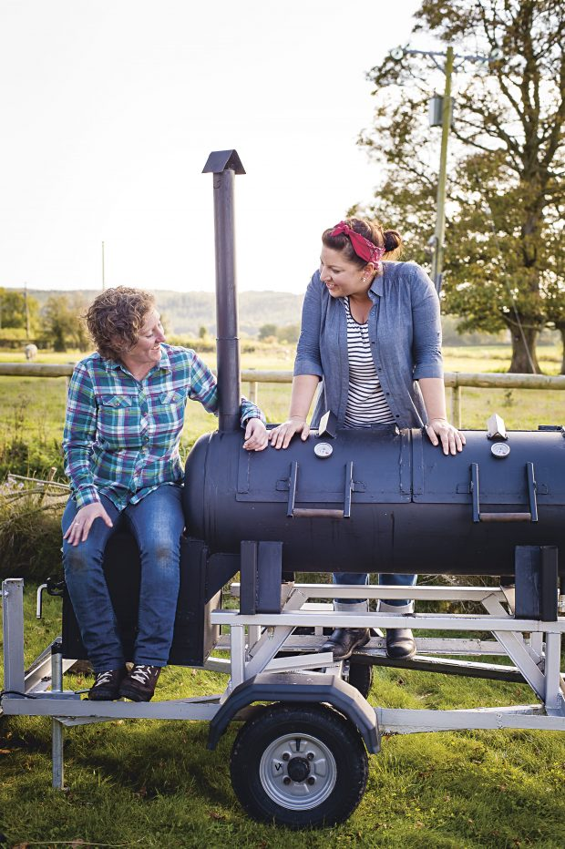 Sam and Shauna by their smoker in a field