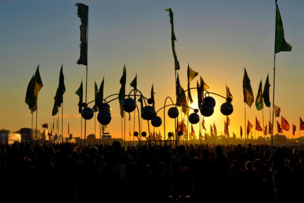 Sunset at Glastonbury with the crowd holding flags