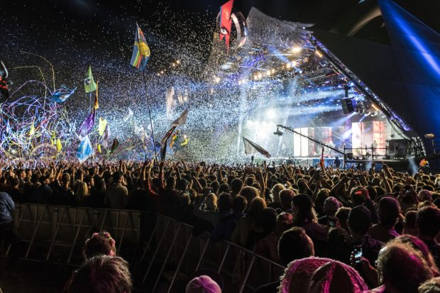 Glastonbury Festival Pyramid Stage at night during a concert with ticker tape floating down on the crowd