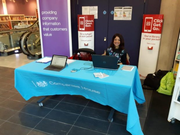 Amanda in a library on a Companies House stall with laptop.