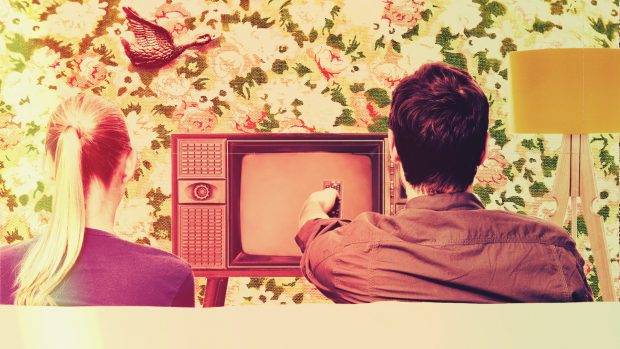 Couple watching TV in typical 1970s setting