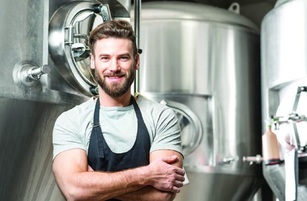 Brewer standing in front of brewing equipment.