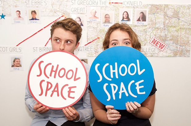 Two students posing behind signs saying 'School Space'