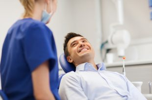 Female dentist with smiling male patient.