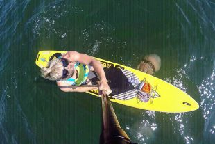 Sarah on her paddle board with a jelly fish.