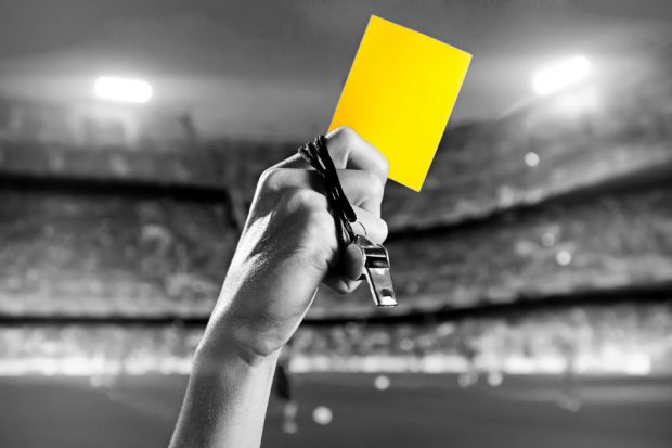 Referee's hand holding whistle and yellow card.