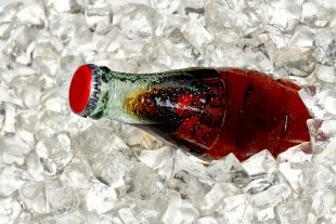 Bottle of cola in crushed ice.
