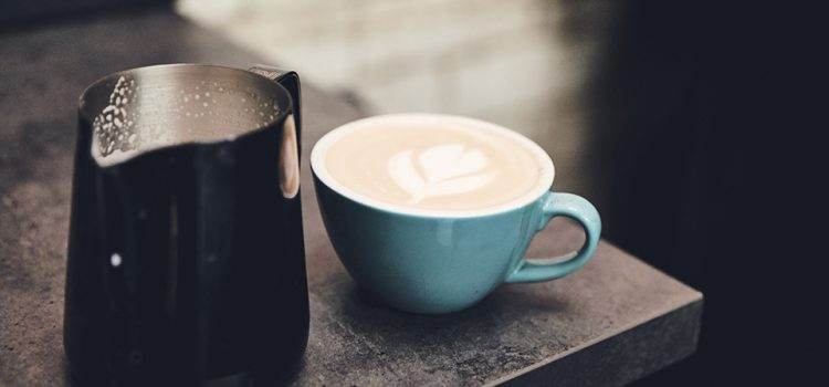 A cup of coffee and jug of milk.