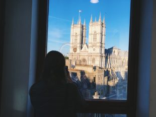 A person's silhouette taking a photo of Westminster Abbey, through a window.