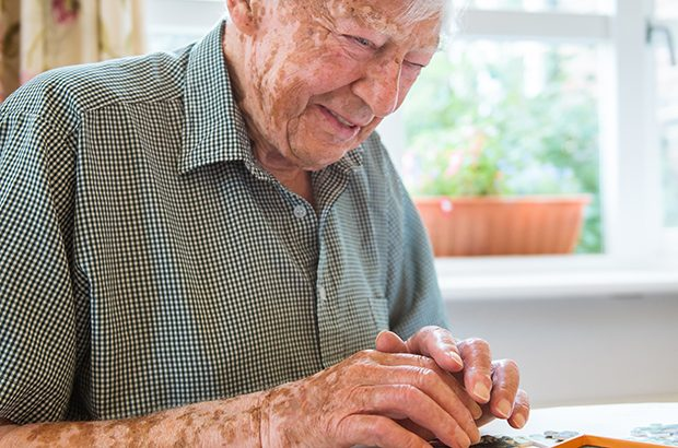 A smiling elderly man completing a puzzle.
