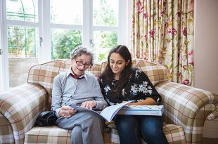 A woman sat on a sofa with an elderly lady reading a book.
