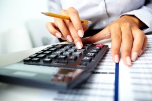 Photo of hands holding pencil and pressing calculator buttons over documents.