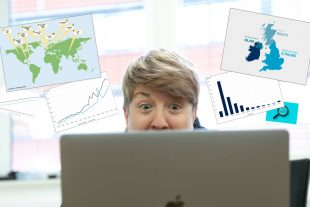 A female looking surprised at a laptop with statistics graphics floating around.