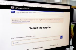 A computer screen displaying Companies House Service with 'Search the register' text.