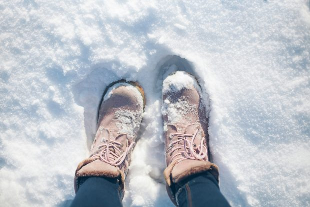 A pair of female boots in the snow.