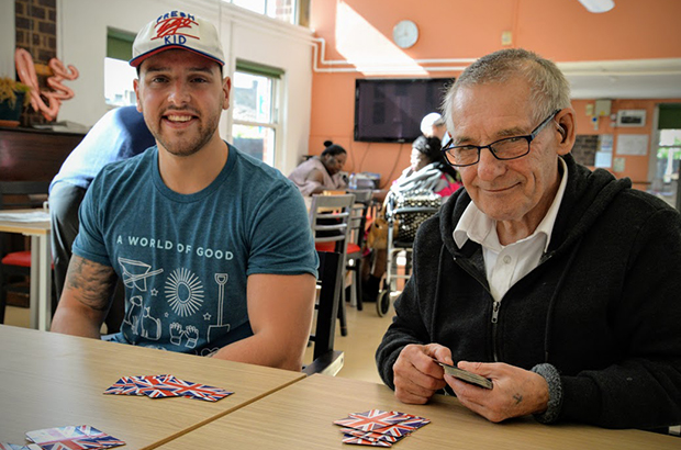 A young volunteer playing cards with an older man at an AGE UK event