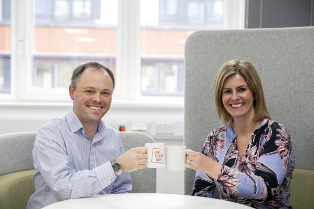 A man and woman holding mugs of coffee and smiling at the camera.