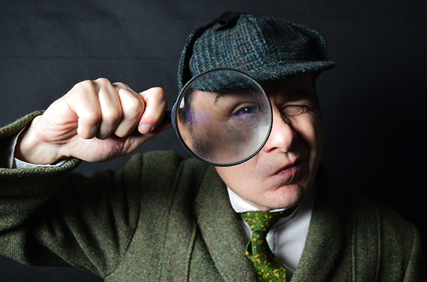 An actor dressed as Sherlock Holmes holding a magnifying glass
