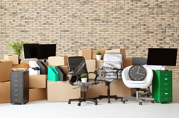An pile of boxes and office furniture in an otherwise empty room