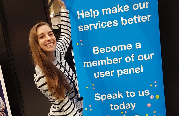 Smiling lady standing next to sign that reads 'Help make our services better, Become a member of our user panel, Speak to us today'
