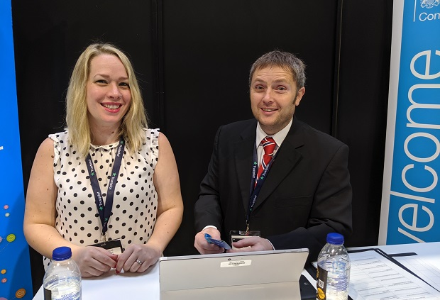 Smiling male and female employees sat behind a desk