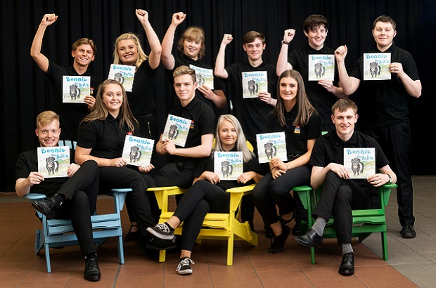 A group of young entrepreneurs in black t-shirts smile at the camera while holding up their 'Bonnie the Beltie' children's book.