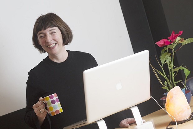 A lady holding a cup of coffee in front of a laptop and smiling.