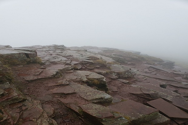 A rocky hilltop almost covered by mist.