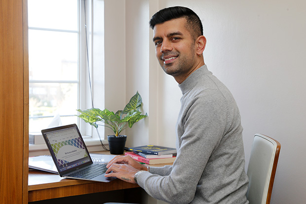A person smiling at the camera whilst working on a laptop at a desk.