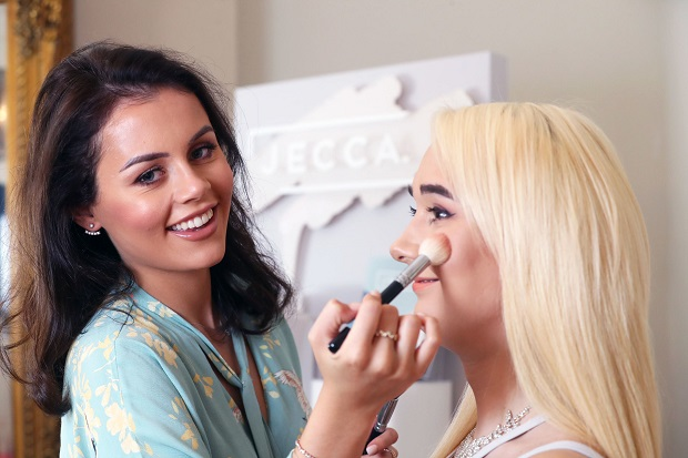 A photo of a lady doing another lady's make up.