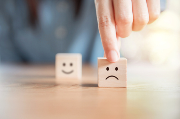 Two cubes with faces drawn on them, one happy and one sad. Person pushing the sad one closer to the camera.