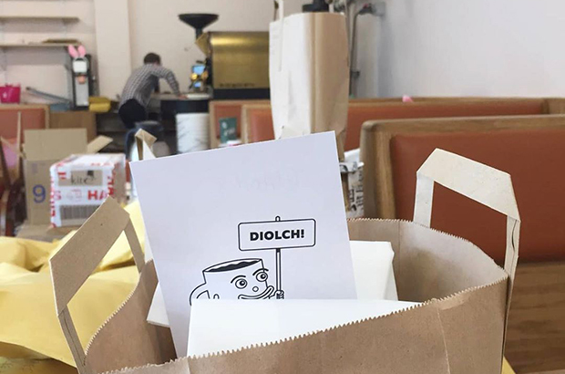 A paper bag with a piece of card displaying a coffee mug and the word 'Diolch' on it.