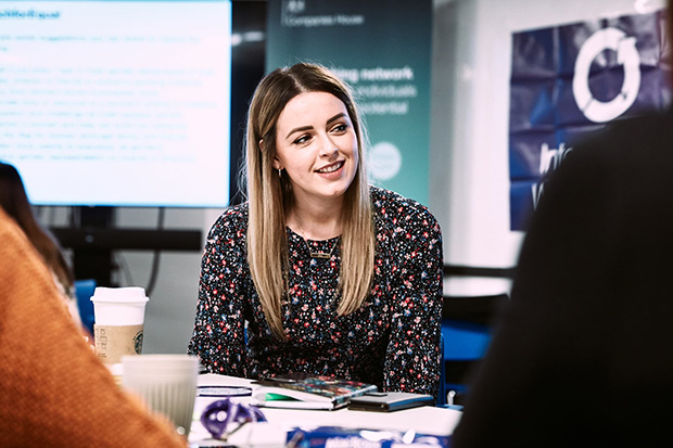 A lady looking to the side and smiling whilst sat at a desk in a conference room.   How Companies House Women's network is championing gender equality Womens network blog post 620x413 1