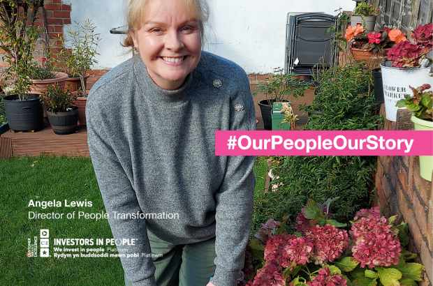 A woman smiling in the garden next to flowers. Text reads: #OurPeopleOurStory, Angela Lewis, Head of People Transformation.