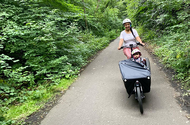 A woman, wearing a helmet, driving a cargo bike in a country lane.