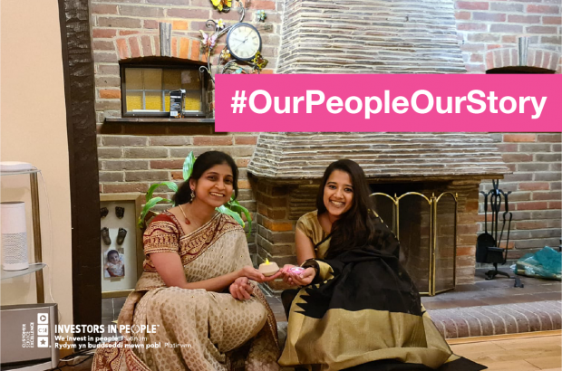 Two people wearing traditional dress sitting down and holding tealights #OurPeopleOurStory